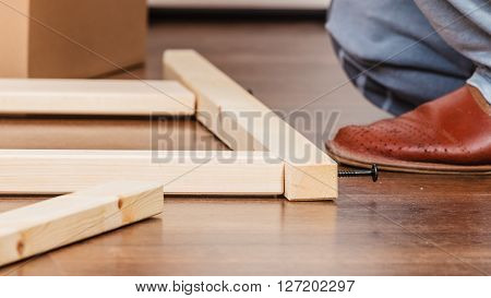 Human assembling wood furniture. DIY enthusiast doing home improvement.