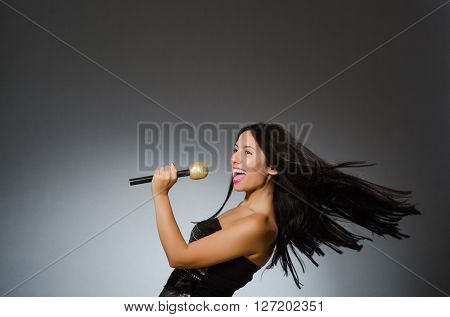 Young woman singing in karaoke club