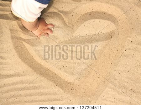 Child Playing With Sand, Drawing A Heart In The Sand