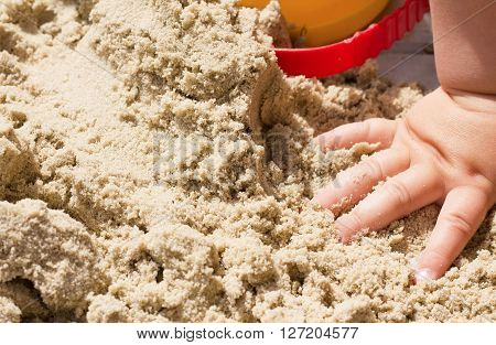 child plays builds towers of sand, sand background