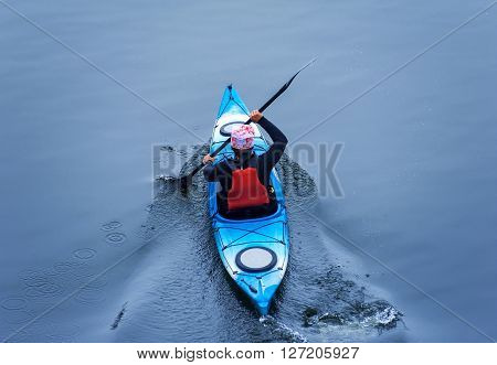 man paddling in a blue kayak is on a river kayaking