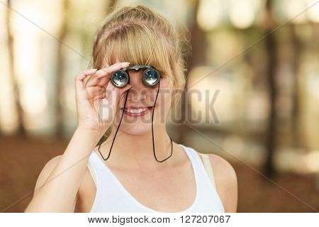 Summer holidays and tourism concept. Lovely tourist woman looking through binoculars n city look forward with pleasure to travel.