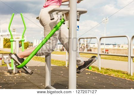 Active woman exercising on elliptical trainer machine. Fit sporty girl in training suit working out at outdoor gym. Sport fitness and healthy lifestyle concept.