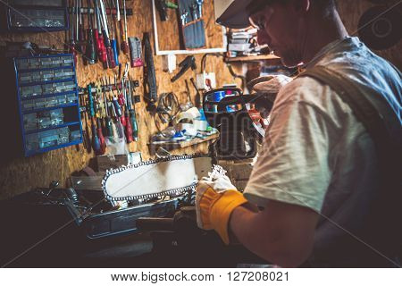 Gasoline Wood Cutter Chain Replacing in a Garage. Men Preparing Tools For Wood Cutter Chain Replacement.