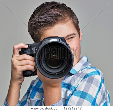 Boy  with dslr camera photographing.  Teen  boy with camera taking pictures.