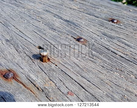 rusty tack in the cracked wood background loose tack in old wood bridge.