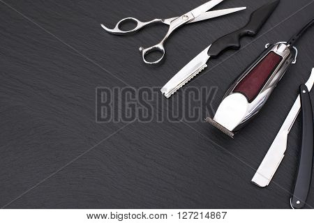 Barber shop equipment on Black background with place for text.  Professional hairdressing tools. Comb, scissor, clippers and hair trimmer isolated.