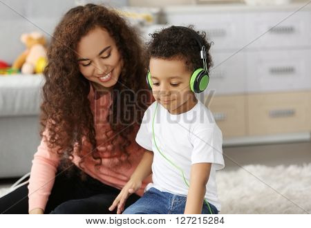 Little boy in headphones and young woman having fun