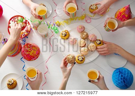 Birthday party with creamy cakes and juice over wooden table background