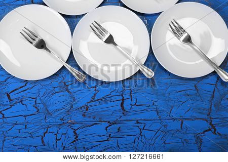 Empty dishes on  blue rustic wooden background.