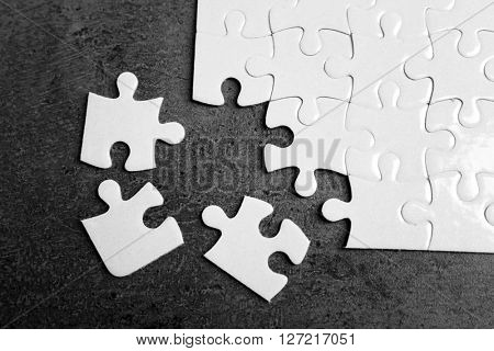 Unconnected white jigsaw puzzle with pieces on grey background