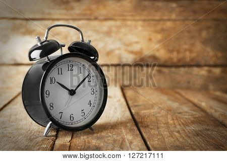 Alarm clock on old wooden table.