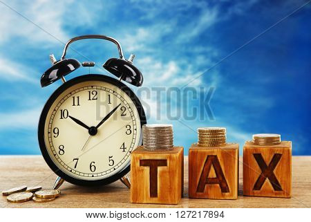 Tax concept. Tax time and alarm clock with coins on table