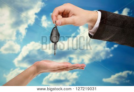 Male hand giving a car key to woman's hand on sky background