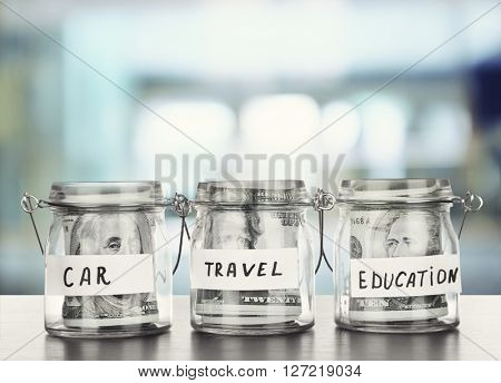 Three jars for different needs full of banknotes on bright background