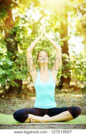 Young beautiful woman doing yoga exercises in park. Retro style