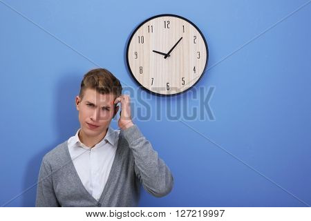 Young handsome man and clock on blue wall