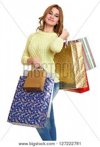 young girl with shopping bag casual dressed blue jeans and a green sweater posing in studio on white background