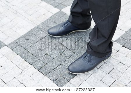 Shoes of a business man standing on street paving stones
