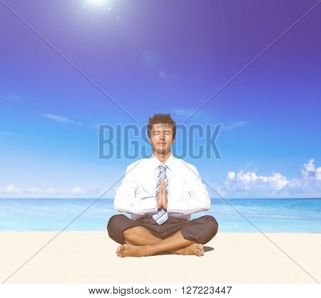 Businessman meditating on the beach.