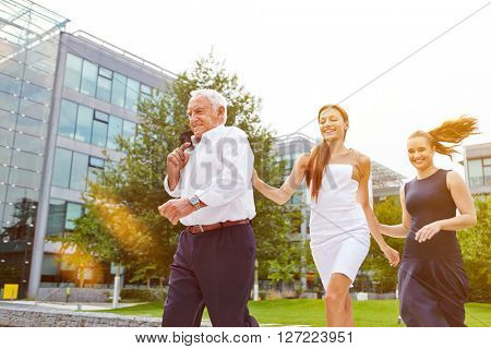 Senior manager and business women running behind each other outdoors