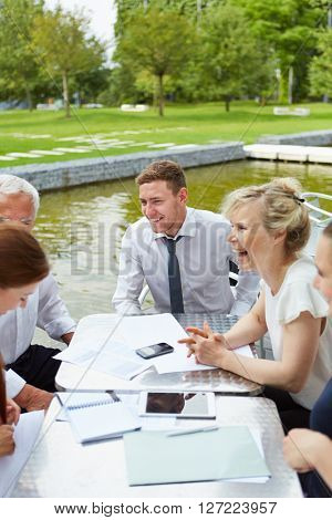 Content business people working together outdoors on a table in summer