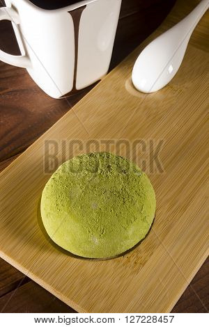 Traditional Japanese mochi with flavor of green tea on a wooden surface and a cup of coffee