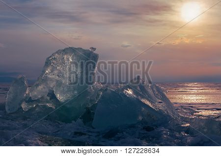 Transparent ice on sunset sky background. Beautiful winter landscape in the Lake Baikal.
