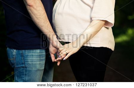 Pregnant woman and her husband holding hands