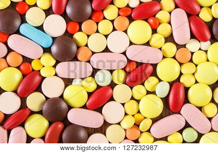 Heap of colorful medical pills capsules or supplements for therapy as background concept of treatment and health care