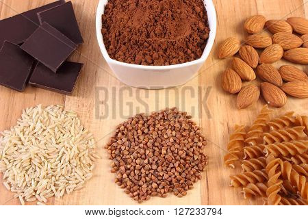 Fresh natural ingredients and products containing magnesium and dietary fiber healthy food and nutrition wholemeal pasta buckwheat brown rice almonds cocoa chocolate