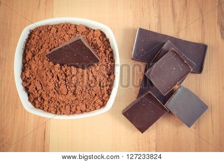 Vintage photo Portion of chocolate and heap of cocoa containing magnesium healthy food and nutrition