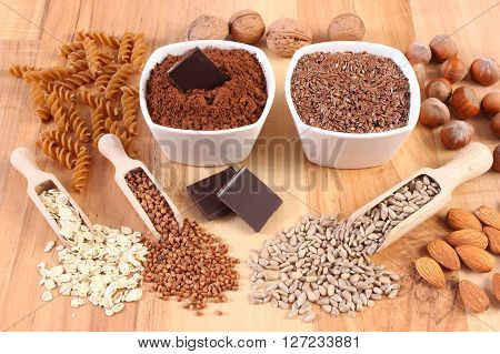 Fresh natural ingredients and products containing magnesium and dietary fiber healthy food and nutrition wholemeal pasta cocoa linseed hazelnut walnut oatmeal buckwheat chocolate sunflower almonds