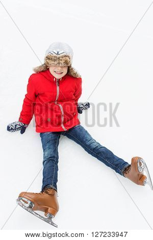 little cheerful boy being silly and enjoying winter fun activities or ice skating at winter vacation or break