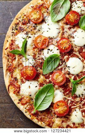 Pizza with cherry tomatoes, mozzarella and fresh basil leaves
