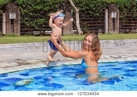 Little happy child in action - active baby swimming with fun and jumping to catching mother hands in swimming pool. Family lifestyle and summer children water sports activity and lessons with parents.
