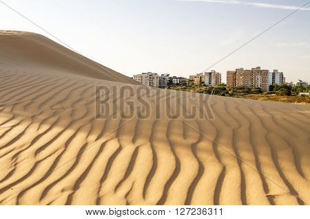 Beautiful photo of a modern city on the border of the desert .
