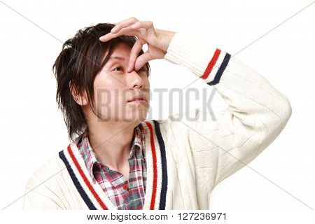 young Japanese man suffers from Asthenopia on white background