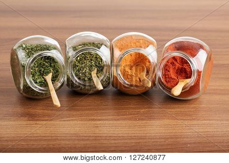 Four glass jar with spices with wooden spoon