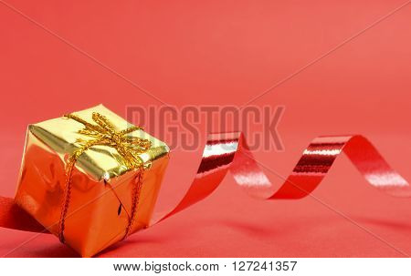 Golden Christmas present with a red ribbon on a red background