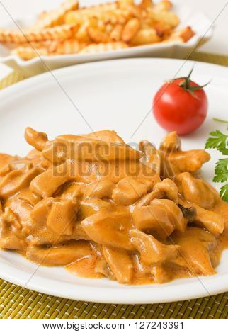 Zurich ragout on a white plate with french fries
