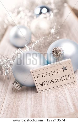 Christmas decoration with a little sign with German Merry Christmas