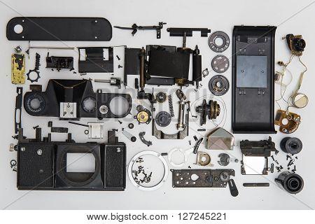 photo camera disassembled parts on white background