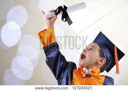 Elementary boy proudly wearing his graduation cap and gown over bokeh background.