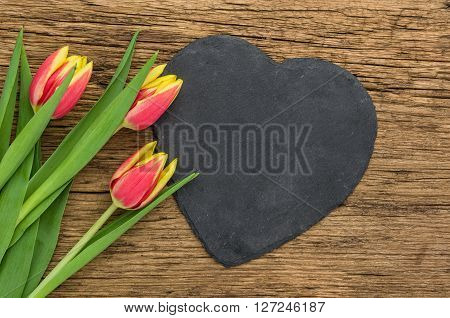 Red Tulips On A  Wooden Background With A Heart-shaped Sign