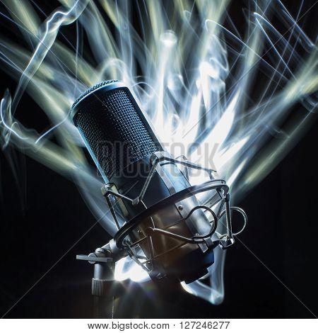 Professional Studio Microphone on black background. light brush