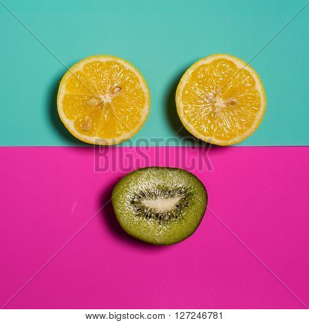 Smiley from the kiwi and lemon on a colored background. Fresh kiwis and lemon fruit interesting fruit composition