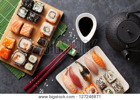 Set of sushi and maki roll and green tea over stone table. Top view