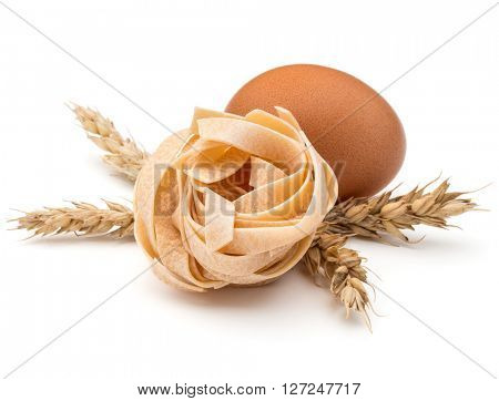 Italian pasta fettuccine nest, egg and wheat ears still life isolated on white background