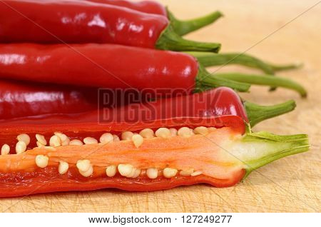 Red chili peppers cut half inside showing seeds on a wood kitchen cutting board